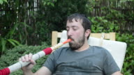 Young man smoking water pipe and drinking tea video