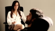 Young man speaking to a therapist while she is taking notes video
