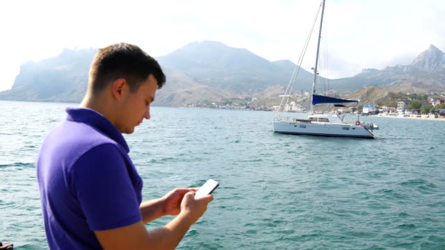 Young man standing near the sea and using smartphone. Yacht in the sea at background. Portrait of handsome guy with mobile phone at ocean beach. He texting sms or chatting in social network. Close up video