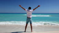Young man standing on  beach with outstretched hands video