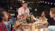 Young man stands to make a toast at an outdoor dinner party video