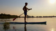 SLO MO Young man stand-up paddleboarding at sunset video