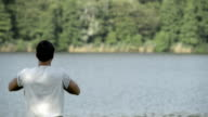 Young man stretching in nature on lake shore in sunny summer day outdoor - HD video footage video