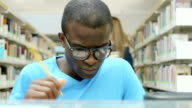 Young man studying in library at school video