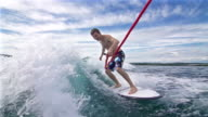 Young man surfing behind a boat, holding onto a rope video