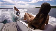 Young man surfing behind a boat, woman sunbathing video