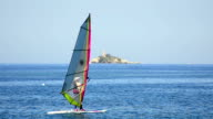 Young Man Surfing the Wind at ocean horizon and island lighthouse at background video