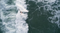 Young man swimming in the stormy ocean and gets hit by the huge danger wave. Directly above aerial drone video. video