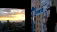 Young man take a picture from mobile phone with glass window over city in slowmotion during amazing sunset video