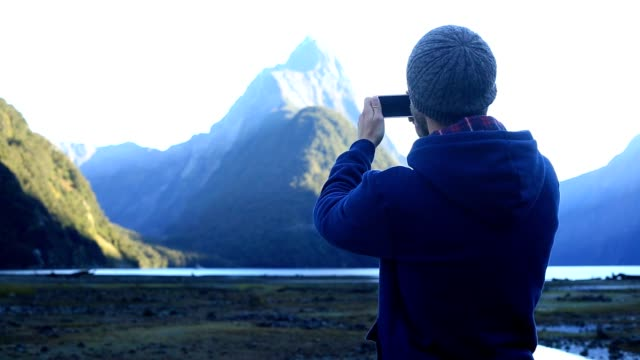 Young man takes a picture of a spectacular mountain landscape with a smart phone video