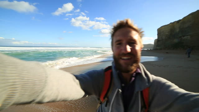 Young man takes a selfie portrait on Gibsons steps beach video