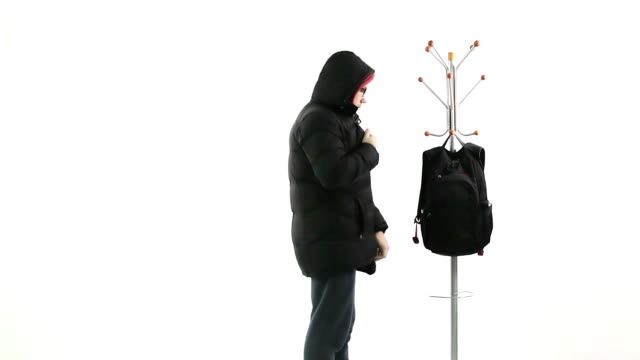 A young man takes off and hangs up the backpack, winter jacket on hanger. video