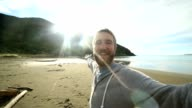 Young man takes selfie portrait on New Zealand's beach video