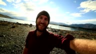Young man takes selfie portrait with a spectacular landscape video