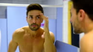 Young man taking care of his face in gym's locker room video
