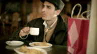 Young man taking coffee break at restaurant after shopping video