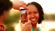 Young man taking pictures of beautiful woman with phone video