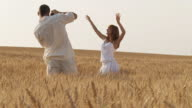 HD: Young man taking pictures of woman posing in wheat video