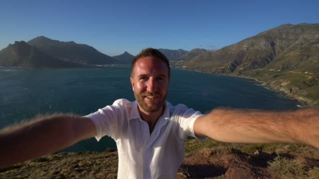 Young man taking selfie with sea view video