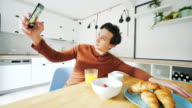 Young man taking selfies in the kitchen. video