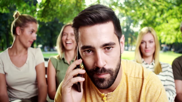 Young man talking at his smartphone while all his friends have fun video