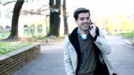 Young man talking by the phone in the city park video