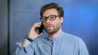 Young man talking on cell phone at modern office video