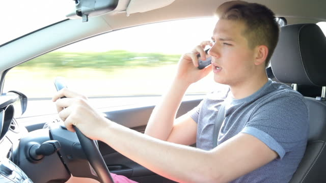 Young Man Talking On Mobile Phone Whilst Driving Car video