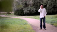 young man talking on phone in the park video