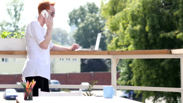 Young Man Talking on Phone, Standing in Balcony Outdoor video