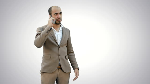 Young man talking on the phone and actively gesturing on white background video