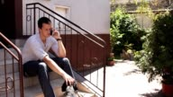 Young man talking on the phone with dog wide video