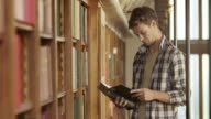 PAN Young man thumbing through a book in library video