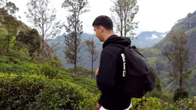 Young man tourist with backpack walking at trail in mountains with beautiful nature landscape at background. Male hiker going along tropical mount road. Healthy active lifestyle. Travel concept video