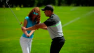 Young man train woman how to hit ball in golf video