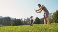 Young man training his dog animal tricks video