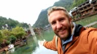 Young man traveling in China takes selfie portrait video