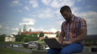 Young man typing on computer, sitting on wall by river. video