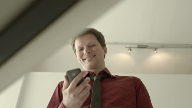 Young man typing sms on smartphone and smiling video