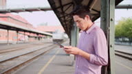 A young man using a tablet while waiting for a train video