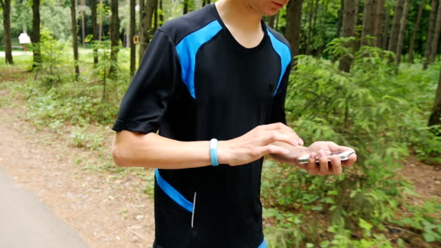 young man using fitness bracelet during morning run video