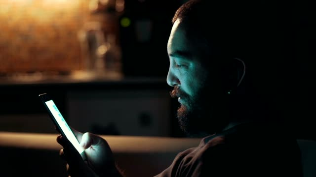 Young man using his smart phone  in the dark video
