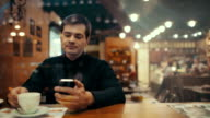 Young man using phone and having coffee in a cafe video