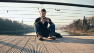 WS Young Man Using Smart Phone On Bridge video