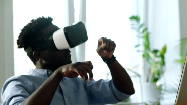 Young man using virtual reality glasses. Reaching high for imaginated object video