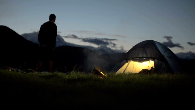 Young man walk in and camp on mountain outdoor at night warming him up with camp fire and walk away - HD video footage video