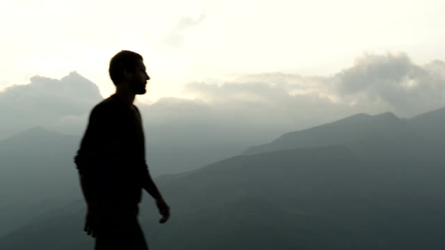 Young man walk on mountain at sunset video HD video
