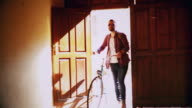 Young man walking in the street with his bike video