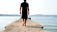 Young Man Walking Pier Fit Vacation Concept HD video