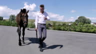 Young man walking with horse near the horse club video